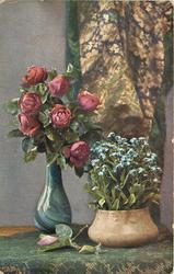 seven red roses in blue  patterned  vase on table  next to bowl of forget-me-nots, curtain behind