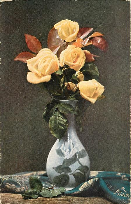 four yellow roses and two buds in blue rose patterned  vase on table partly covered with white patterned blue cloth,green leaves hang down left and right