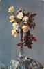 seven yellow roses in slender tall glass vase on stand covered with white patterned blue cloth,brown leaves hang down right
