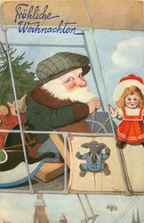 Santa wearing a green cap piloting airship carrying presents, tree, doll sits front, elephant puppet dangles