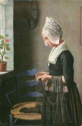 DES FISCHERS TOCHTER  woman stands examining a net
