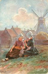 two Dutch girls sit on ground in front of distant windmill