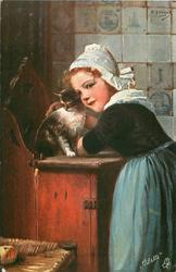girl leans on wooden counter stroking cat, both look down & left