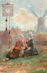 KNITTING FATHER'S SOCKS  two Dutch girls sit on ground in front of distant windmill