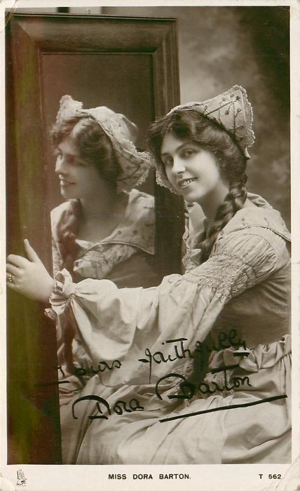 MISS DORA BARTON  holds mirror  with both hands ( reflection shown), faces left looking front