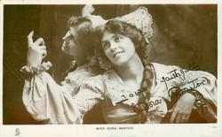 MISS DORA BARTON  leans against mirror ( reflection shown), faces front looking up