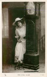 MISS ETHEL OLIVER  standing by grandfather clock
