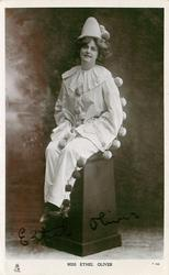 MISS ETHEL OLIVER  sitting on pedestal in clown costume, looking front & up