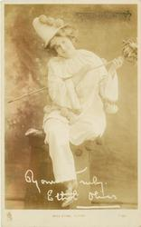 MISS ETHEL OLIVER  sitting on pedestal in clown costume, holding sceptre, looking front