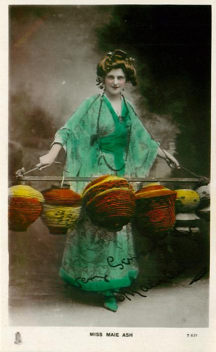 MISS MAIE ASH  in Japanese costume holding lanterns hanging from pole