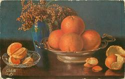 four oranges in brass dish, another beside with peel, peeled slices in glass dish, blue vase of flowers behind