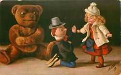 TEDDY HAT DAS NACHSEHEHEN  boy doll kneels before girl doll standing with arms outstretched, teddy left