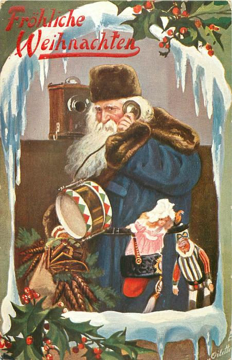 blue coated Santa carrying many toys uses telephone, facing & looking left, framed by snow & holly