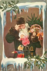 green coated Santa carrying many toys & tree looks front, framed by snow & mistletoe