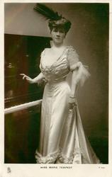 MISS MARIE TEMPEST  standing beside piano