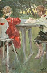 two children sit at table reading, boy facing left, girl faces away