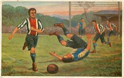 man in red striped kicks ball away, player on ground with legs in air