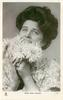 MISS JEAN AYLWIN  head & shoulders, holds dahlias up to face with both hands