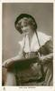 MISS NINA SEVENING  sitting holding folder with both hands, facing partly left, looking front