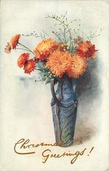 orange mums in tall blue vase