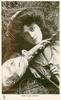 MISS HILDA ANTONY  as farm girl, holding rake with both hands while lying in hay