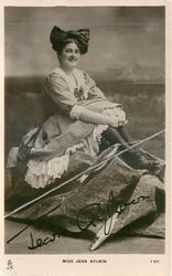 MISS JEAN AYLWIN  sits on rock, fishing line & fish front