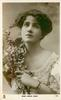 MISS JESSIE ROSE  head & chest, holding branch with blossom,  faces front, looks up