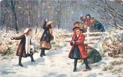 girls having snow ball fight with girls across wooden fence