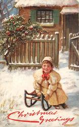 boy in white sitting on sled