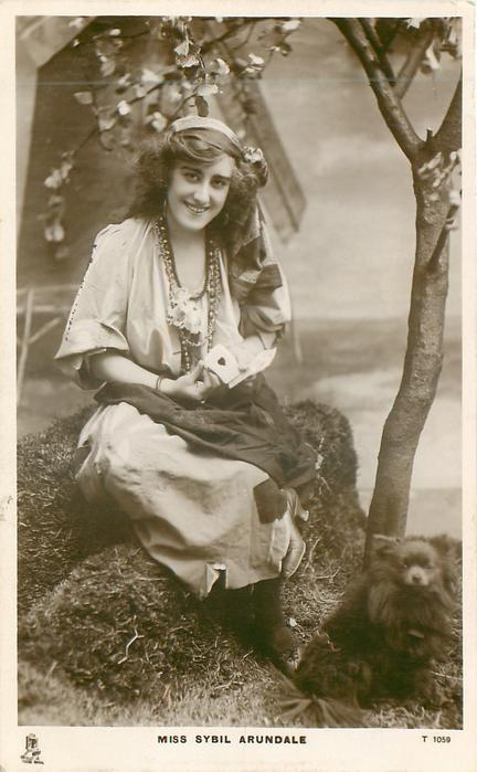 MISS SYBIL ARUNDALE  as gypsy, sitting holding playing cards, showing ace of hearts, chihuahua at feet