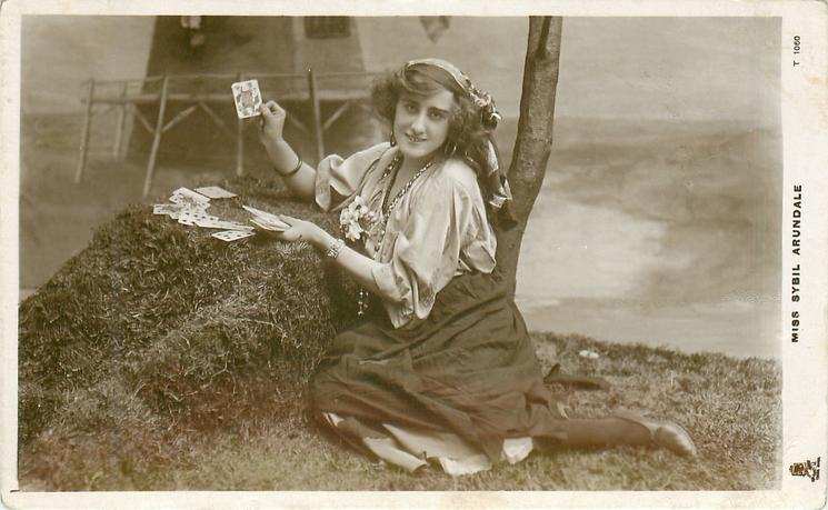 MISS SYBIL ARUNDALE  as gypsy, sitting holding playing cards, showing queen of hearts