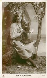MISS SYBIL ARUNDALE  as gypsy, sitting holding playing cards, with chihuahua under her arm