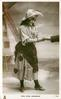 MISS SYBIL ARUNDALE  as gypsy, stands reading a palm