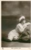 MISS FLORENCE WARD (Tuck error for WARDE) at seaside, leaning on rock, facing & looking right