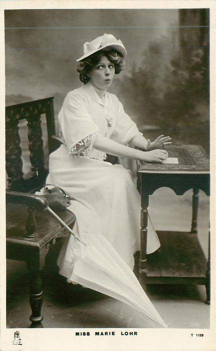 MISS MARIE LOHR  sits writing at table, facing right, looking front