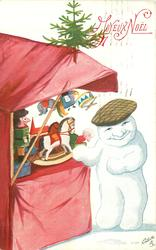 snow person faces front beside stall of puppets for sale, small toy horse on stall, Xmas tree above