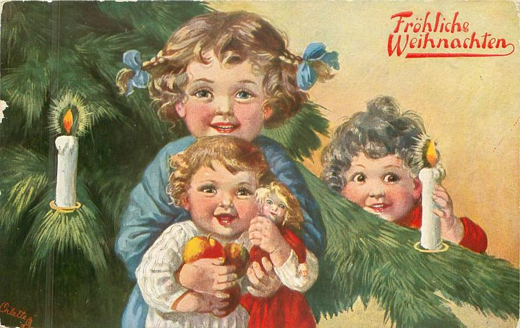 three young girls beside & in front of leafy  xmas tree, two lit candles, child in front carries doll & apple