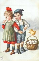 boy puts white egg in hand of girl coyly facing left, chick on handle of egg basket on ground