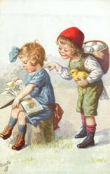boy taps back of girl facing left & sitting reading EASTER book, chick in his hand & egg basket on his back