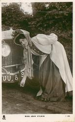 MISS JEAN AYLWIN  bending down as if to start car