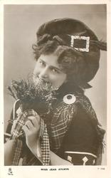 MISS JEAN AYLWIN  Scottish attire, head & shoulders, holding heather with both hands, facing left looking front