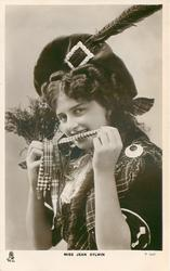 MISS JEAN AYLWIN  Scottish attire, head & chest, holding heather, ribbon across mouth, facing mostly left, looking front