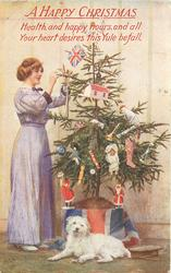 A HAPPY CHRISTMAS  (woman in purple dress stands to left of Xmas tree, dog lies in front)