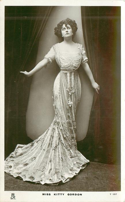 MISS KITTY GORDON  standing holding curtains apart, looking up