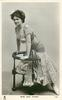MISS JEAN AYLWIN  kneeling & leaning on chair-back, facing left looking front