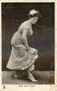 MISS JEAN AYLWIN  stands bent forward facing right, looking front, holding up skirt