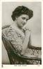 MISS JEAN AYLWIN  seated in wicker chair, hands clasped in front of her, facing right, looking front