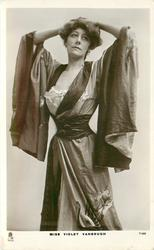 MISS VIOLET VANBRUGH  standing with both hands on top of her head