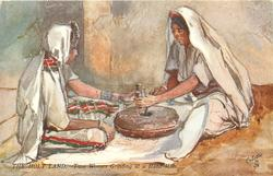 TWO WOMEN GRINDING AT A HAND-MILL