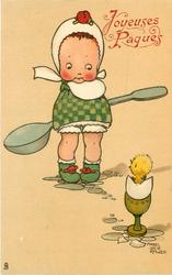 girl in green chequered dress holds large spoon behind her back, chick in shell in egg-cup looks apprehensive